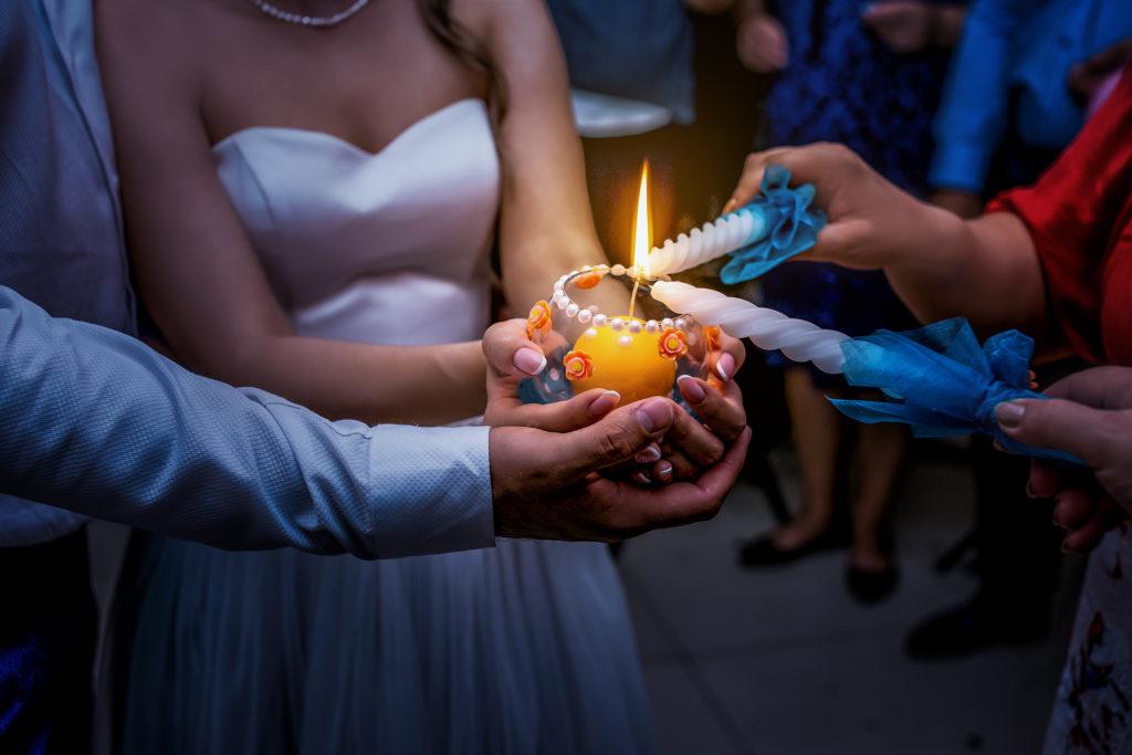 Свадебная фотосъемка от свадебного фотографа на свадебном банкете. Молодые зажигают свечи.